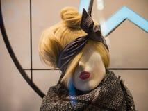 Kvinnlig skyltdocka i en peruk med en sjalett som binds på hennes huvud Arkivfoton