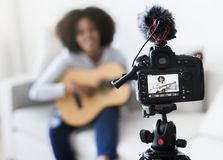 Kvinnlig släkt TV-sändning för bloggerinspelning musik hemma royaltyfri bild