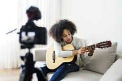 Kvinnlig släkt TV-sändning för vloggerinspelning musik hemma royaltyfri foto
