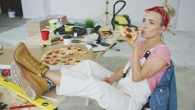 Kvinnlig snickare som äter pizza på arbetsplatsen