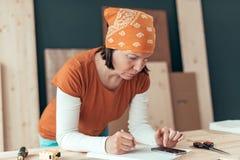 Kvinnlig snickare som g?r finansiell ber?kning arkivfoto