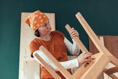Kvinnlig snickare som reparerar trästolplatsen i seminarium arkivbild