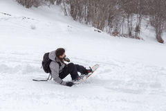 Kvinnlig snowboarder som spelar med hennes snowboard Arkivbilder