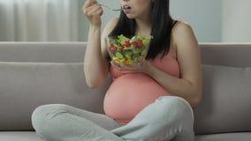 Kvinnlig som är gravid med barnsammanträde på soffan som äter sallad, sund banta jämvikt stock video