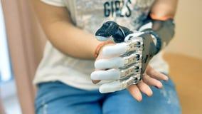 Kvinnlig som använder den futuristiska robotic cyborgarmen Verklig modern medicinsk robotic protes lager videofilmer