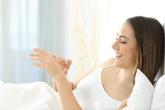 Kvinnlig som applicerar fuktighetsbevarande hudkrämkräm på hennes händer i morgonen royaltyfri foto