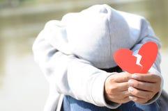 Kvinnlig som erbjuder bruten hjärta i händer arkivbild