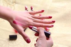 Kvinnlig som försöker olika kupor av läppstift på henne Fotografering för Bildbyråer