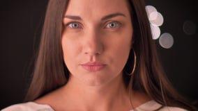 Kvinnlig som fast håller ögonen på in i kameran på enljus bakgrund lager videofilmer
