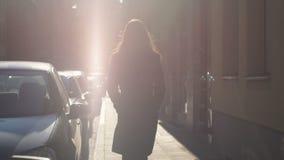 Kvinnlig som går säkert ner gatan in mot solljus till lycklig framtid, långsam-mo stock video