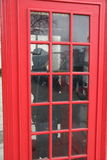 Kvinnlig som gör en appell i den brittiska röda PhoneBoxen arkivbilder