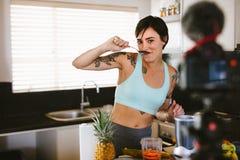 Kvinnlig som gör en vlog om sunda smoothies arkivbilder