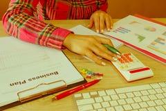 Kvinnlig som i regeringsställning studerar plan Affärskvinna som fungerar på kontoret beräkna eller kontrollera jämvikt Affärspla Royaltyfria Foton
