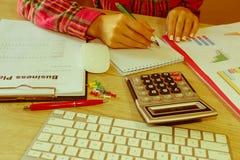 Kvinnlig som i regeringsställning studerar plan Affärskvinna som fungerar på kontoret beräkna eller kontrollera jämvikt Affärspla Royaltyfria Bilder