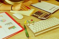 Kvinnlig som i regeringsställning studerar plan Affärskvinna som fungerar på kontoret beräkna eller kontrollera jämvikt Affärspla arkivbild