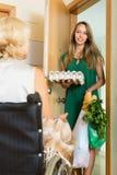 Kvinnlig som kommer med mat till ogiltigt Arkivbilder