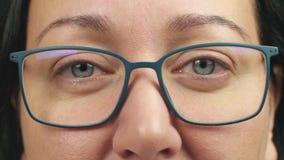 Kvinnlig som ler ögon i exponeringsglas som ser in i extremt slut för kamera upp stock video