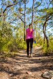 Kvinnlig som promenerar ett buskespår bland naturen arkivbild