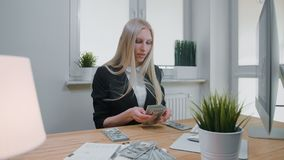 Kvinnlig som räknar pengar på kontorsarbetsplatsen Härlig ung blond kvinna i affärsdräkten som i regeringsställning sitter på lju stock video
