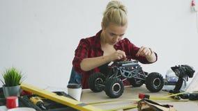 Kvinnlig som reparerar denkontrollerade bilen arkivfilmer
