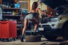 Kvinnlig som reparerar en bil arkivbild