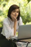 Kvinnlig som ser hennes bärbar dator i en utomhus- coffee shop Arkivfoto