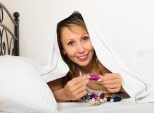 Kvinnlig som äter sötsaker i säng Arkivbild