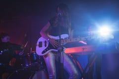 Kvinnlig som utför på upplyst etapp i nattklubb Royaltyfri Bild