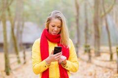 Kvinnlig som utomhus använder mobiltelefonen Arkivbild