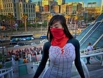 Kvinnlig Spiderwoman Cosplayer i stads- inställning royaltyfria bilder