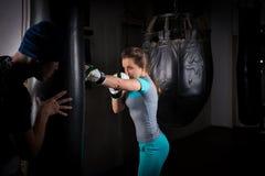 Kvinnlig sportig boxare i boxninghandskar som utbildar med hennes soffa och Arkivbild