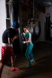 Kvinnlig spoty boxare i boxninghandskar utbilda med hennes instruktör Arkivbilder
