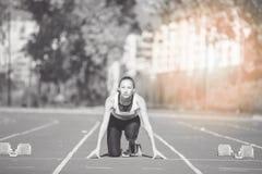 Kvinnlig sprinter som får klar att starta loppet arkivbilder