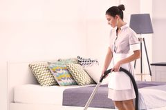 Kvinnlig städerska för hotell med rengöringsmedlet arkivfoto