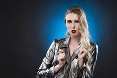 Kvinnlig stående i ett silvrigt metalliskt till ett omslag på blå bakgrund Arkivfoton