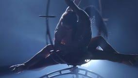 Kvinnlig stabilisator i beige liggande hängning för body tillbaka på flyg- beslag på svart bakgrund silhouette långsam rörelse cl stock video