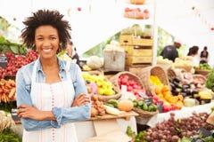 Kvinnlig Stallhållare på marknaden för ny mat för bönder arkivbilder
