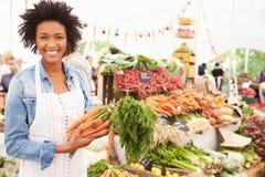 Kvinnlig Stallhållare på marknaden för ny mat för bönder Arkivfoton