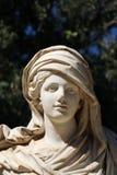 Kvinnlig staty i en trädgård Arkivfoto