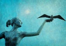 Kvinnlig staty som släpper fågeln Arkivbild