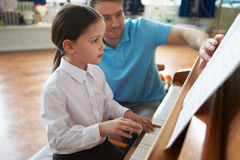 Kvinnlig student Enjoying Piano Lesson med läraren arkivfoto