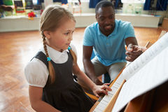 Kvinnlig student Enjoying Piano Lesson med läraren royaltyfri fotografi