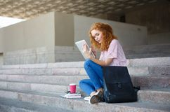 Kvinnlig student för ung rödhårig man som arbetar med minnestavlan som utomhus sitter på trappan Arkivbild