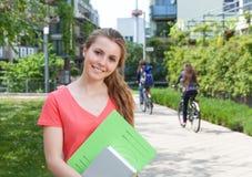 Kvinnlig student i en röd skjorta med skrivbordsarbete på universitetsområde Royaltyfri Fotografi