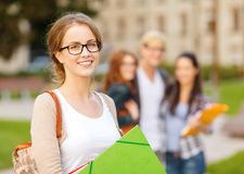 Kvinnlig student i eyglasses med mappar Arkivfoton