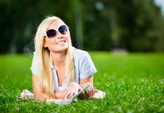 Kvinnlig student i solglasögon med boken på gräset royaltyfria bilder