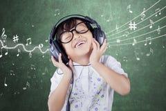 Kvinnlig student Listening Music Arkivfoto
