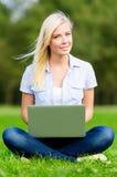 Kvinnlig student med bärbar datorsammanträde på gräset royaltyfri bild
