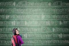 Kvinnlig student med den stora bokhyllan royaltyfria bilder
