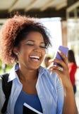 Kvinnlig student Reading Text Message på mobilephonen Arkivbilder